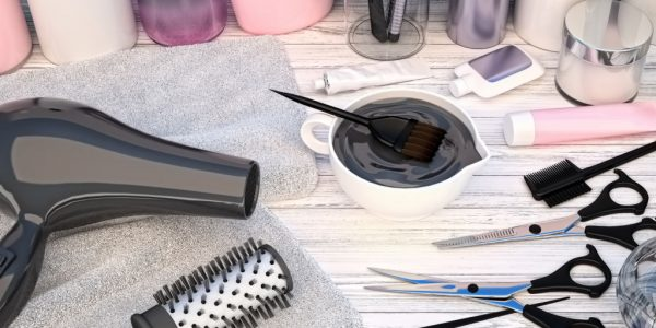 Hair cutting shears, combs, hair dye and professional cosmetics for hair located on a wooden table.